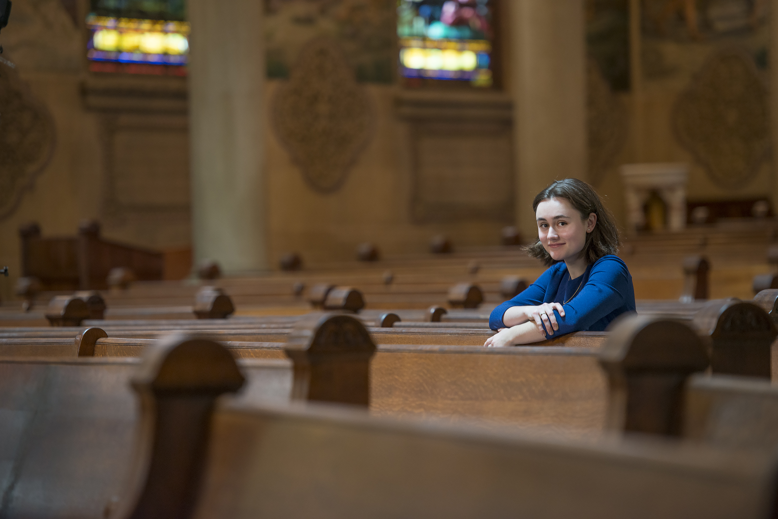 Student Christina E.C. Smith photographed among the pews in Memorial Church. (Smith studies medieval wood carvings called misericords.)