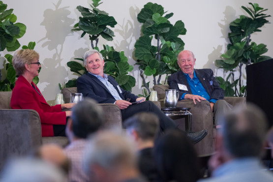 Three members of a panel in front of an audience.