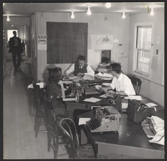 Black and white image of students around table working on typewriters.
