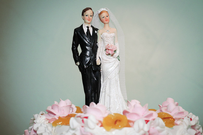 bride and groom figures atop wedding cake