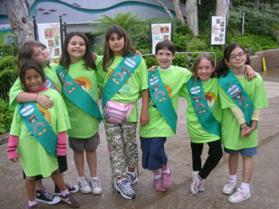 A row of Girl Scouts in green T-shirts and Scout sashes