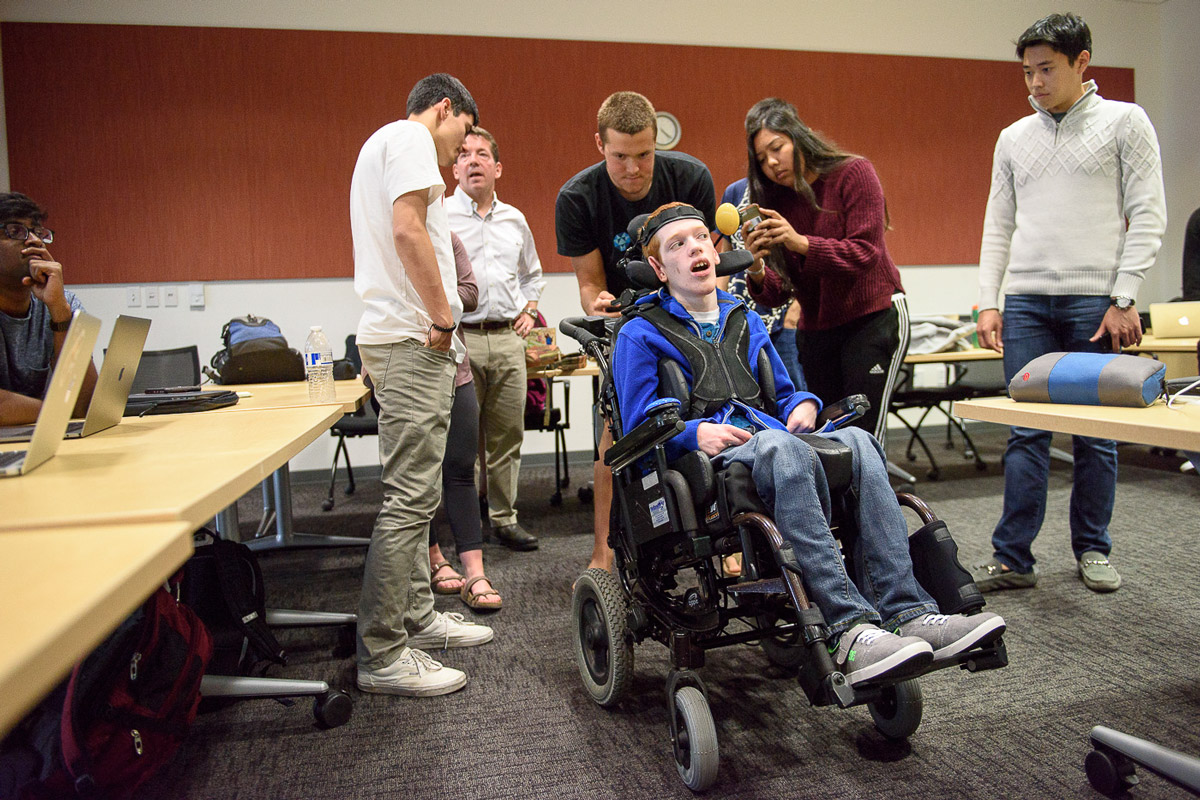 Students in the Compassionate Design class taught by John Moalli take photos of the wheelchair used by Zach Crighton, a 17-year-old high school student with cerebral palsy. The students are hoping they can make improvements to his wheelchair and communications tools.