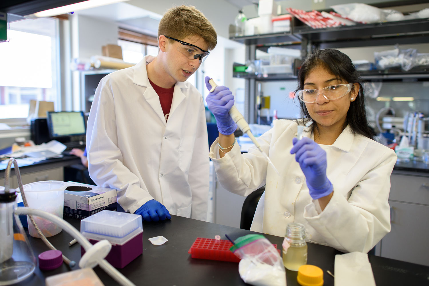 Chris Lindsay, left, a doctoral candidate in materials science, works one-on-one with Blanca Jaime, a high school student, in a laboratory.