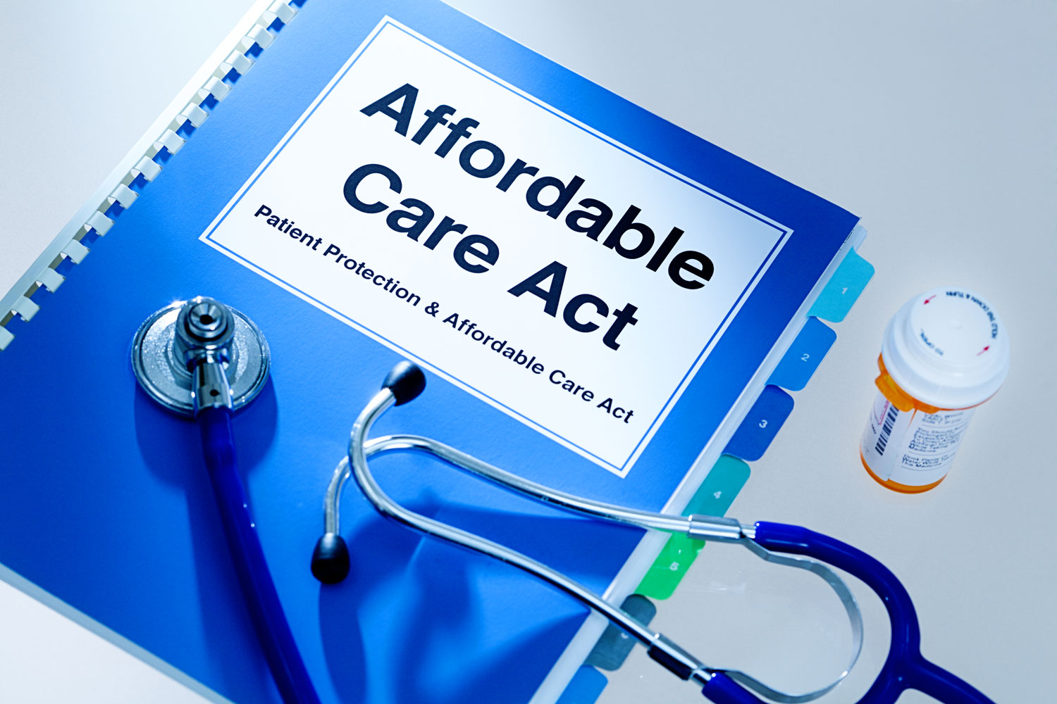 photo of a binder titled Affordable Care Act with stethoscope, pill bottle