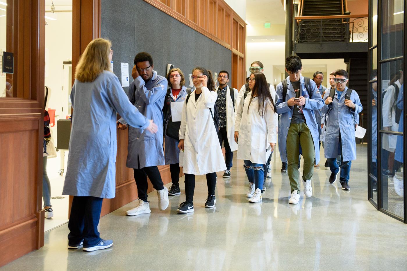 Jennifer Schwartz Poehlmann, senior lecturer in chemistry, left, welcomes the Leland Scholars to their first lab at Stanford.