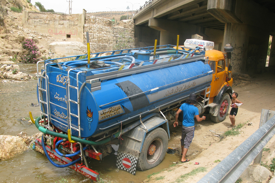 c870a4104 A tanker truck illegally takes water from a river in Jordan.