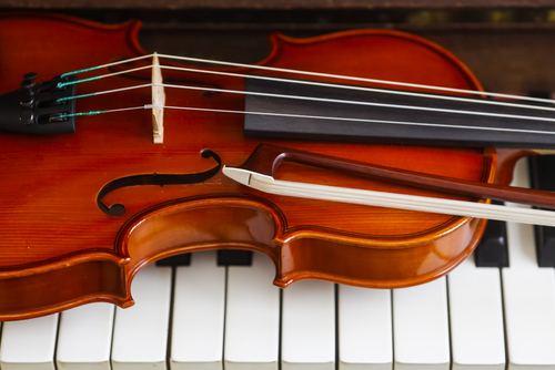 Photo of a violin and bow on piano keys