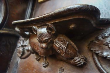 This carving of a cat playing the fiddle is located in Wells Cathedral in Wells, Somerset, England.
