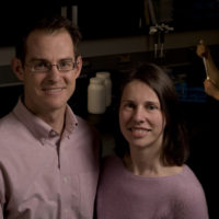 A man and woman stand together in a lab.