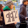 woman at protest holding a sign saying 'I am the 99 percent' / miker/Shutterstock