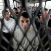 Immigrants on a U.S. Immigration and Customs Enforcement bus heading for deportation / AP Photo/LM Otero