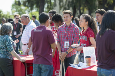 students chatting at a resource fair information table