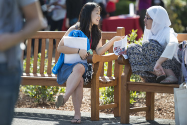 two prospective students chatting on bench