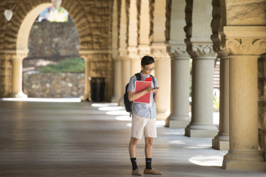 a student stands alone in the arcade of the main quad