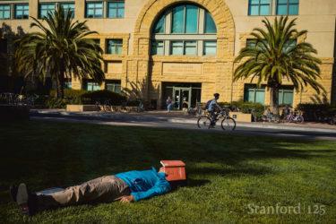 Student lying on grass.