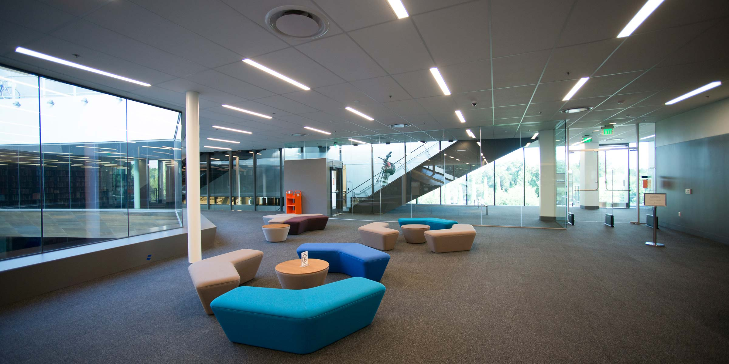 Three groupings of upholstered benches in turquoise, blue, beige and brown stand next to round end tables in an open space near the library's main desk, with glass walls and windows in the background.) (Image credit: L.A. Cicero)