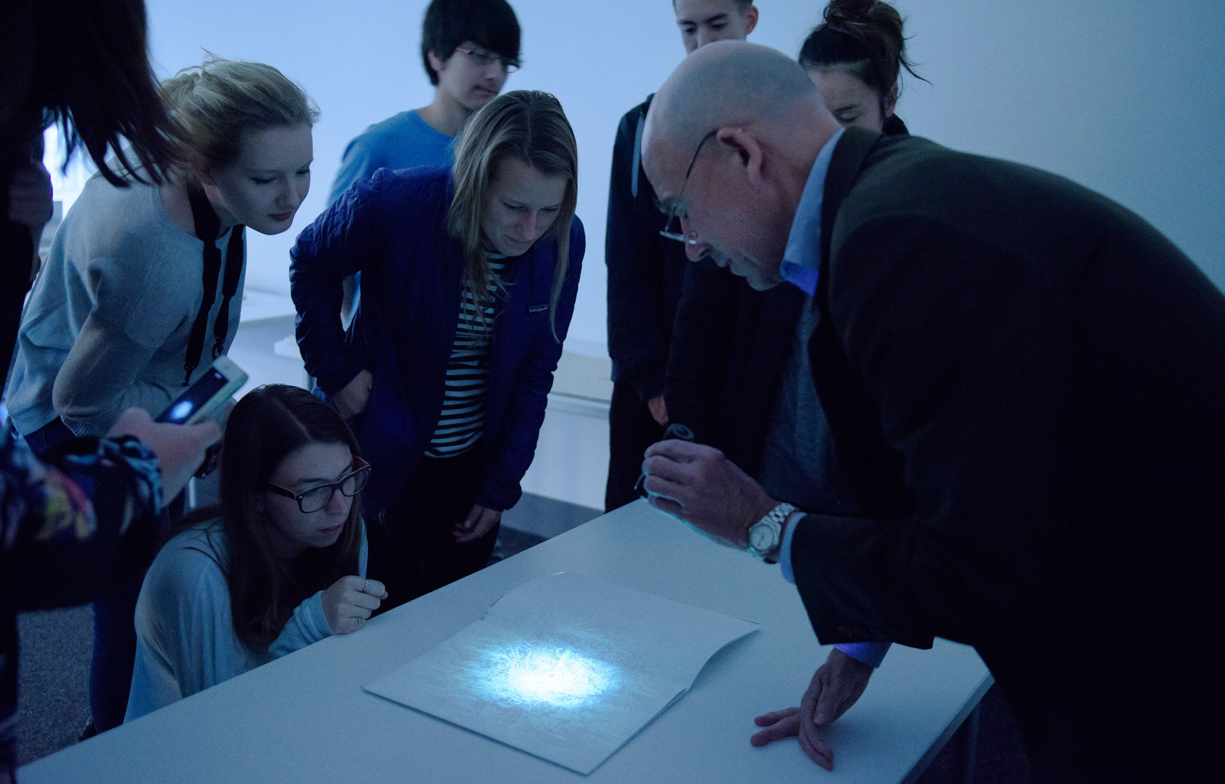 Undergraduate students, crouching, leaning and standing around a table as a male librarian dressed in a dark suit jacket and blue dress shirt focuses a beam of light from a very small UV flashlight on a page in 2013 (Image credit: L.A. Cicero)