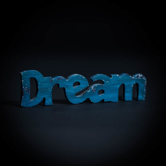 "Wood cutout, painted blue, spelling the word ""Dream"""