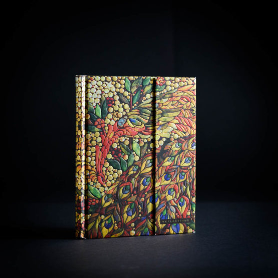 An ornate journal with a shimmery peacock pattern of golds, reds, blues and greens on the cover