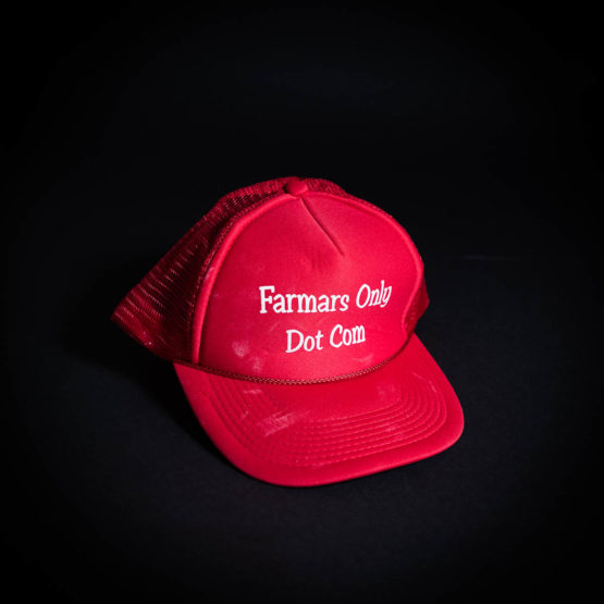 "Red hat with ""Farmars Only Dot Com"" printed on it"