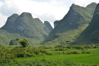 Karst mountains in China with farmer in field.