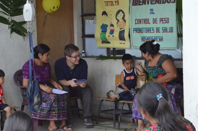 Research assistant Alejandro Chavez works with mothers and health promoter in a health center in Guatemala
