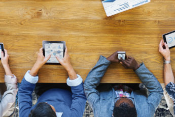 overhead view of people sitting around a table using various phones, tablets, etc.