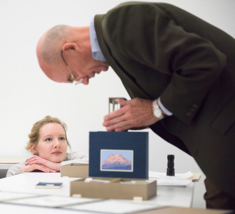 Hadley Nelson, an undergraduate student with blond hair kneels on the floor, her chin resting on her hands on top of the table, as she watches Peter Blank, dressed in a dark suit and blue shirt bending a 10-inch cube covered in dark blue silk with a hand-colored image of Mount Rainier. It is an artist's book titled Local Conditions: One Hundred Views of Mount Rainer – At Least. (Image Credit: L.A. Cicero)
