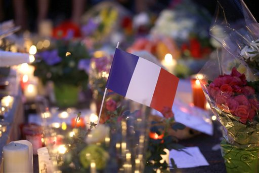 French flag amid candles and flowers