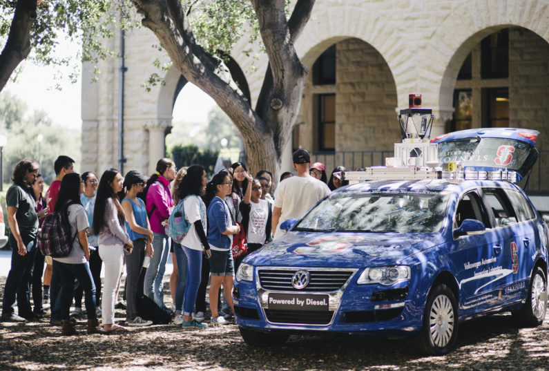 Students gathering at demonstration of an autonomous car