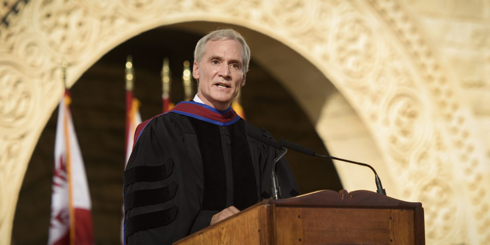 Marc Tessier-Lavigne at the podium with flags and arches in the Main Quad in the background.