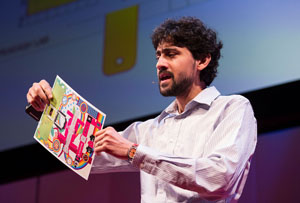 Manu Pakrash holds an origami-stype paper microscope on stage at TED