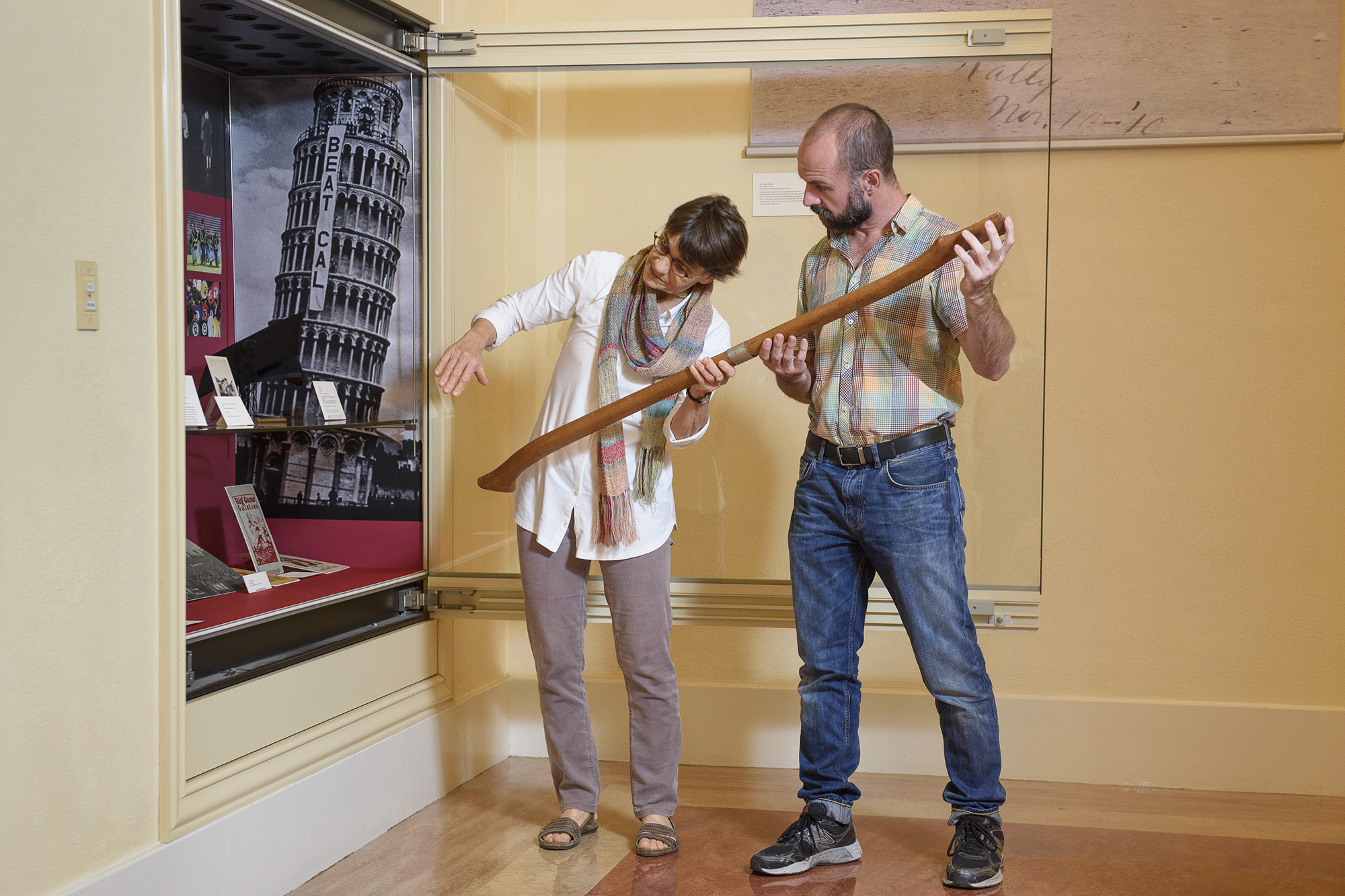 Exhibition designer Becky Fischbach and archivist Daniel Hartwig placing handle of Stanford Axe in display case at Green Library