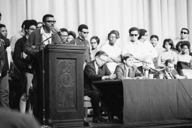 Members of the Black Student Union take the stage and microphone during a program following the assassination of Martin Luther King, Jr., April 8, 1968