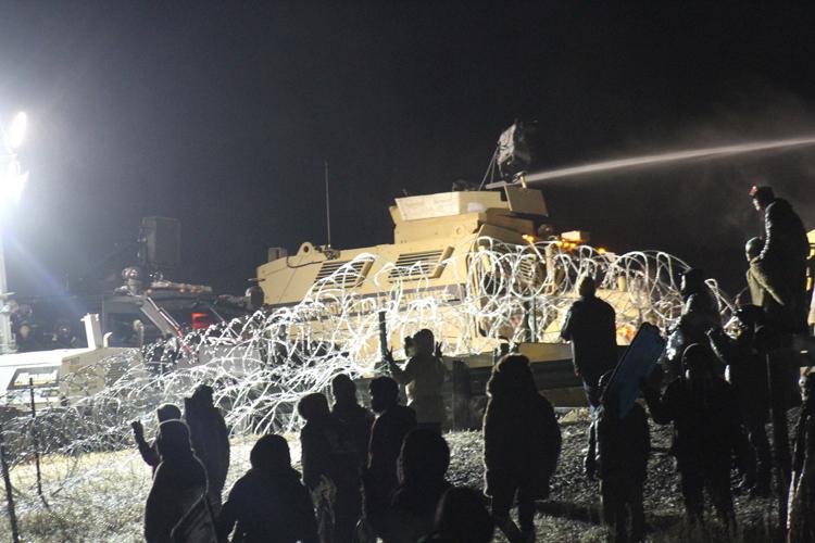 Law enforcement personnel fire a water cannon at Standing Rock protestors in sub-zero temperature.