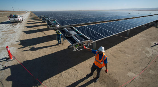 Workers starting a robot on a solar panel.