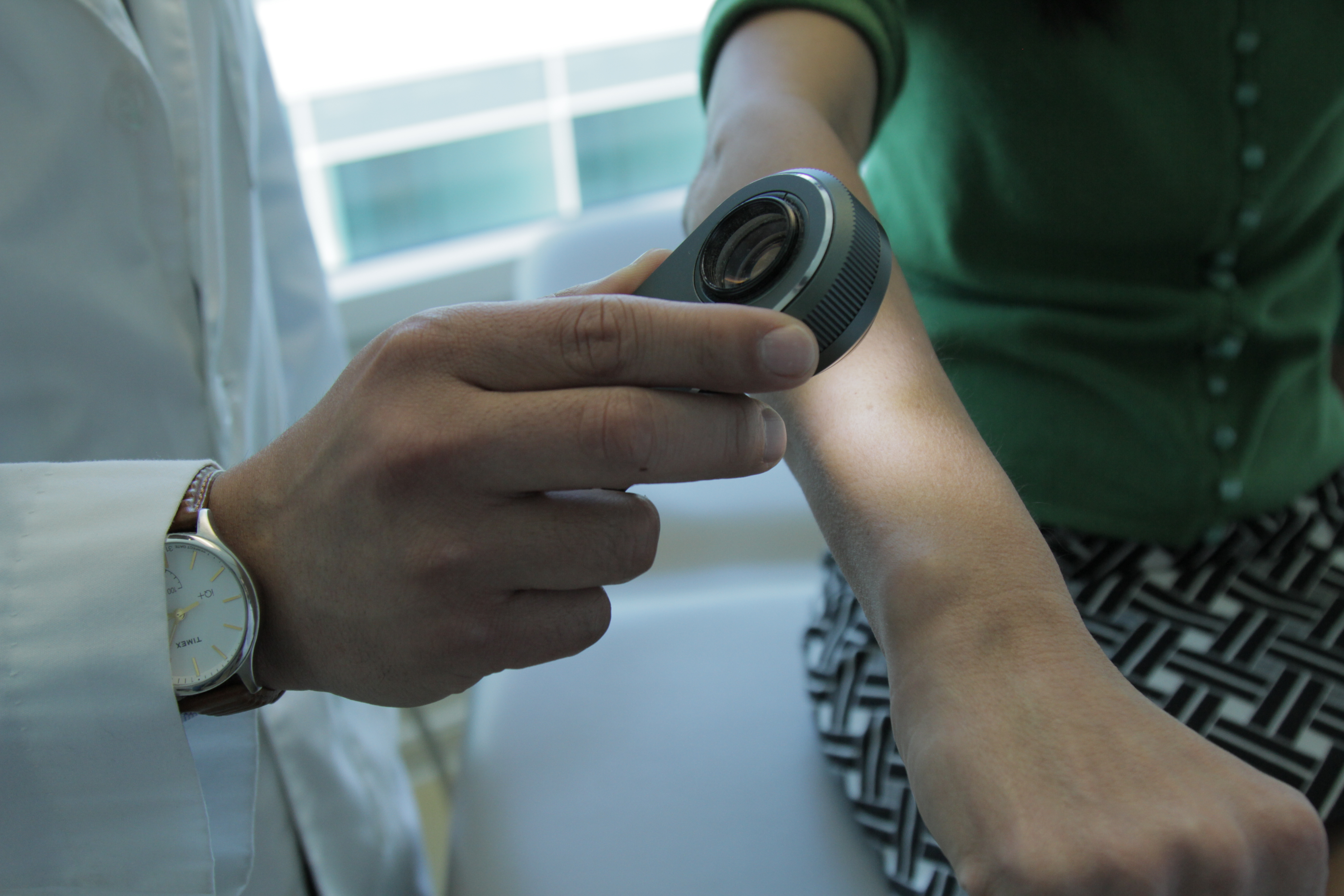 Dermatologist using a dermatoscope to look at skin