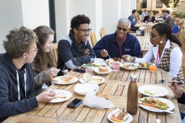 students and family members gathered for lunch at outdoor table