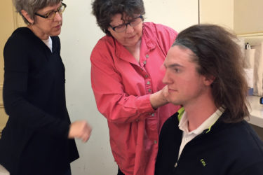 For a production of Shakespeare's The Tempest, Costume designer Connie Strayer and wig designer Kerry Rider-Kuhn fit Prospero's wig on Tim Schurz.