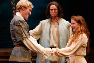 In a production of Shakespeare's The Tempest, Miles Petrie and Emma Rothenberg are Ferdinand and Miranda, while Tim Schurz as Prospero looks on.