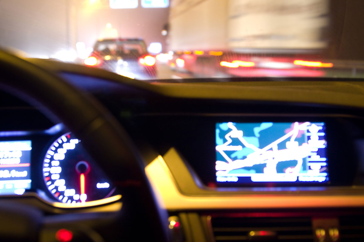 car dashboard and navigation system illuminated at night