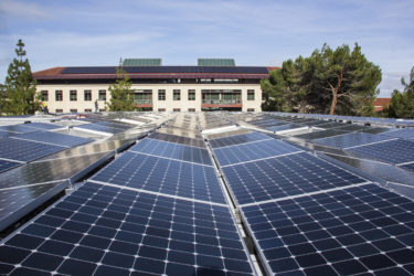 solar panels atop the Hansen Experimental Physics Lab with view toward the photovoltaics on the Huang Engineering Building.