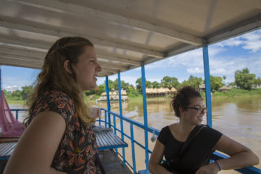 two young woman seated on a boat, traveling down a muddy river
