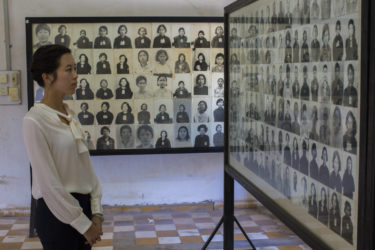a young woman viewing walls of photos of victims of the genocide