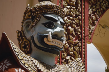 close-up of the face of an ornately carved and painted wooden statue