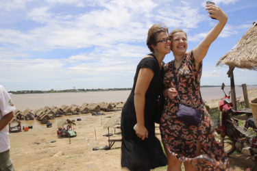 two women taking a selfie in front of thatched roof huts and the Mekong river