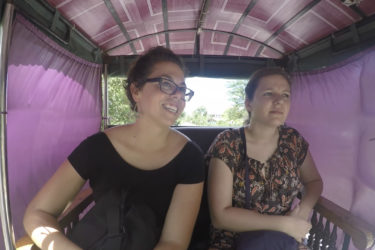 two woman seated in a narrow carriage covered with fabric