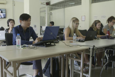 people working on laptops as they observe a televised trial