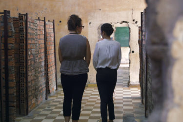 two women walking away down a hallway