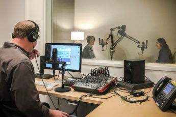 Michael Osborne, audio production director in a sound studio with students Megan Shea and Isha Salian practicing interview skills